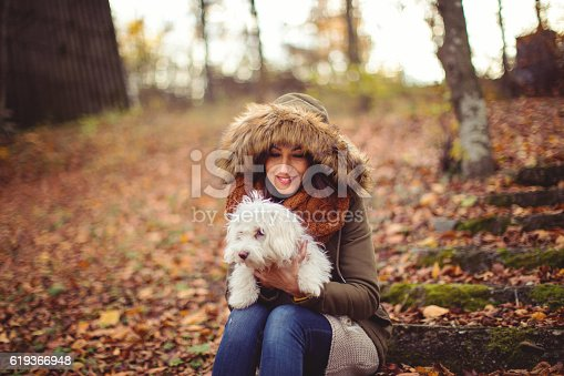 Young woman with the hood sitting in the park and holding a dog,autumn