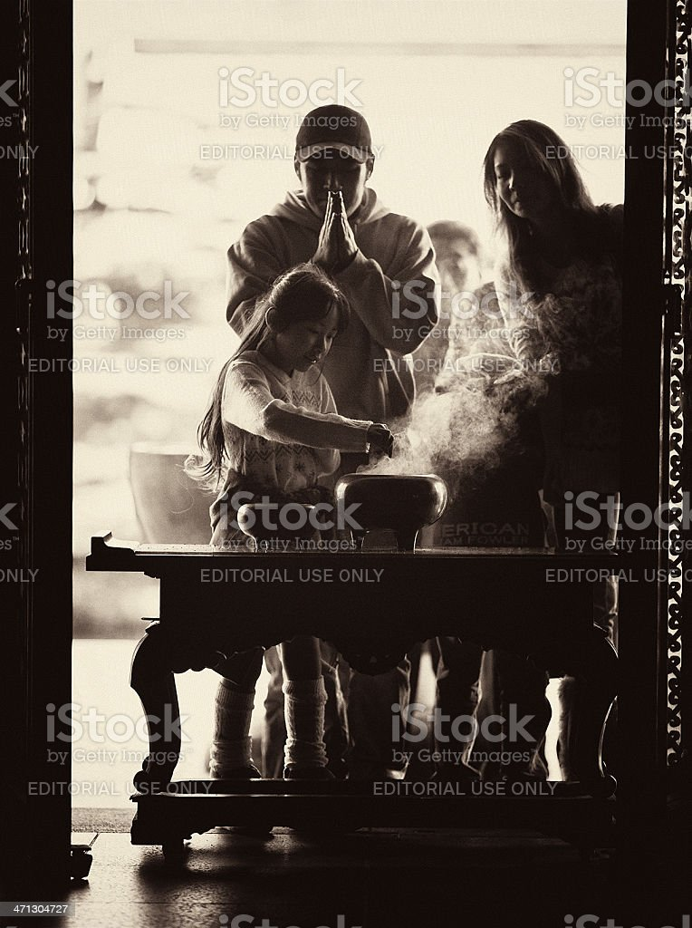 girl and adult couple offering incense royalty-free stock photo