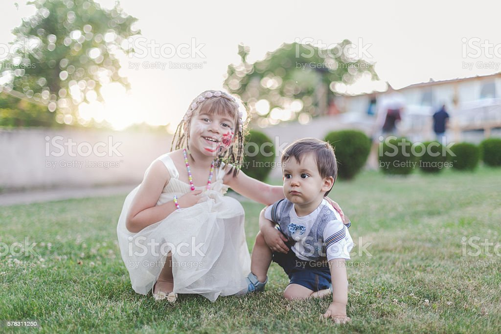girl and baby boy smiling stock photo
