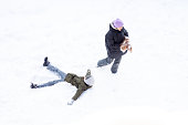 girl and boy are having fun outdoors, day is snowing, sister and brother laughing dog play snow in winter warm clothes. Top view