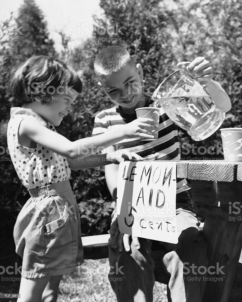 Girl and boy at lemonade stand royalty-free stock photo