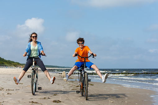 Girl and boy biking on beach