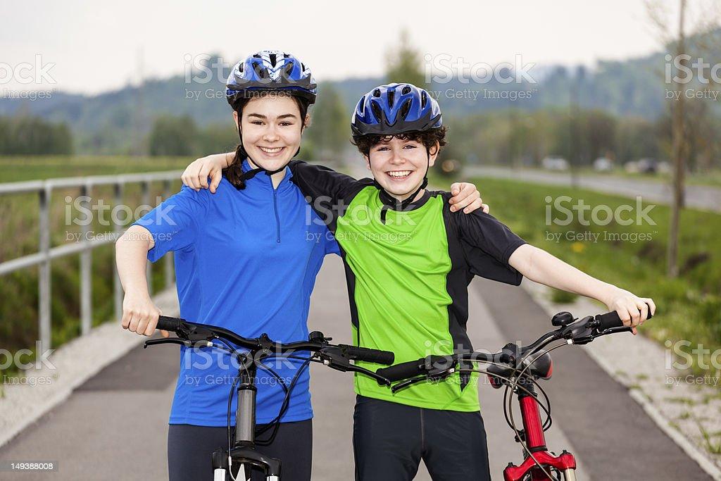 Girl and boy biking stock photo