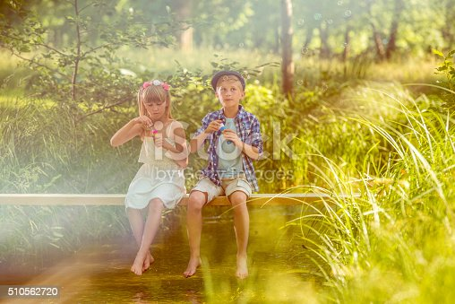 618034312 istock photo Girl and boy blowing soap bubbles above a stream 510562720
