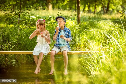 618034312 istock photo Girl and boy blowing soap bubbles above a stream 510562760