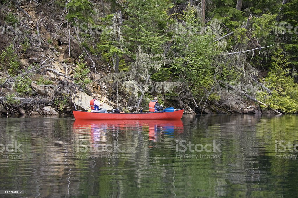 Girl and boy canoeing near the shore royalty-free stock photo