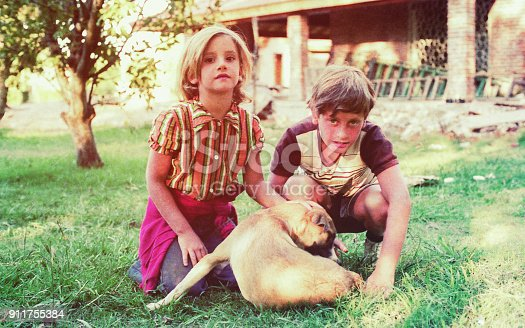 Vintage image from the seventies of a girl and boy playing with their dog ourdoors.