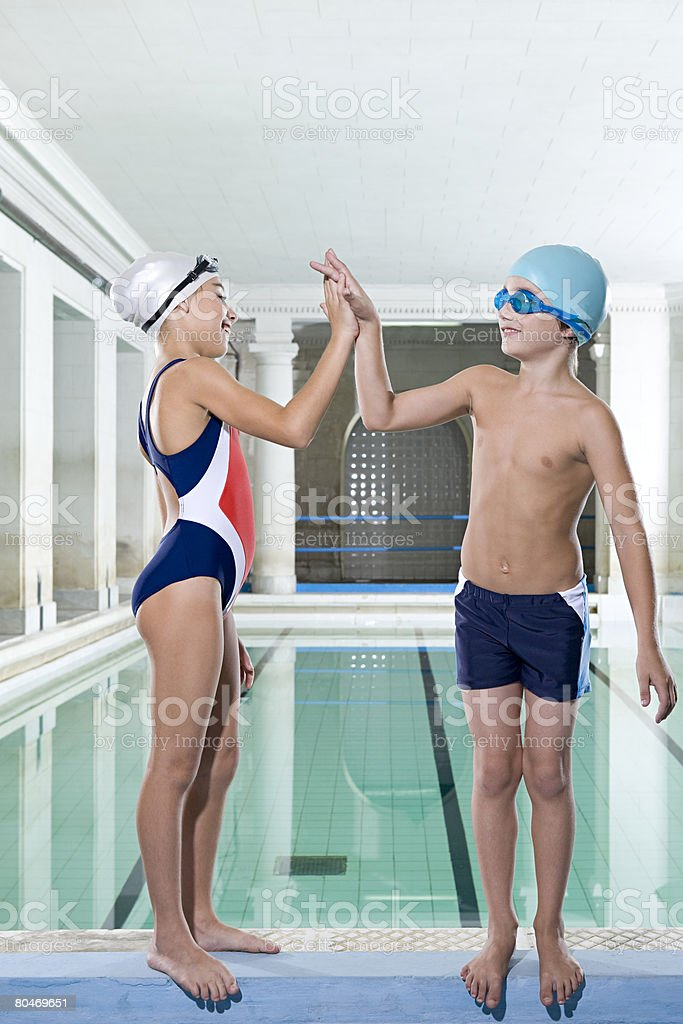 A girl and boy high fiving stock photo