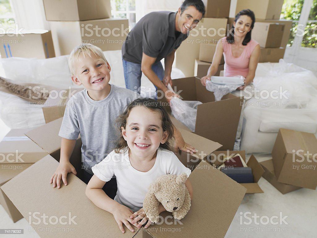 Girl and boy in cardboard box in house with boxes with man and woman in background stock photo