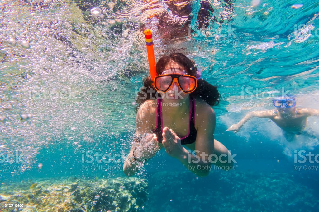 Girl and boy in swimming mask dive in Red sea near coral reef stock photo