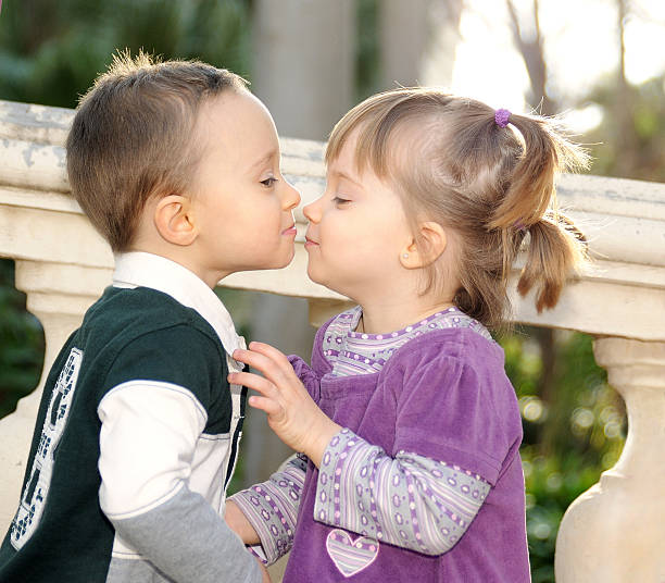 girl and boy kissing tenderly in the park - little girls little boys kissing love stock photos and pictures