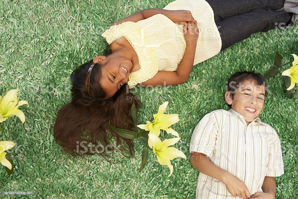 Girl and boy (6-11) lying on grass with flowers, smiling, view from above 免版稅 stock photo