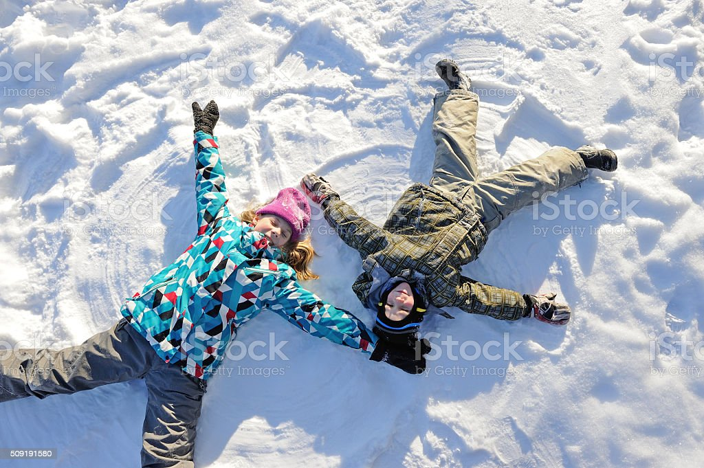 Girl and boy lying on snow stock photo