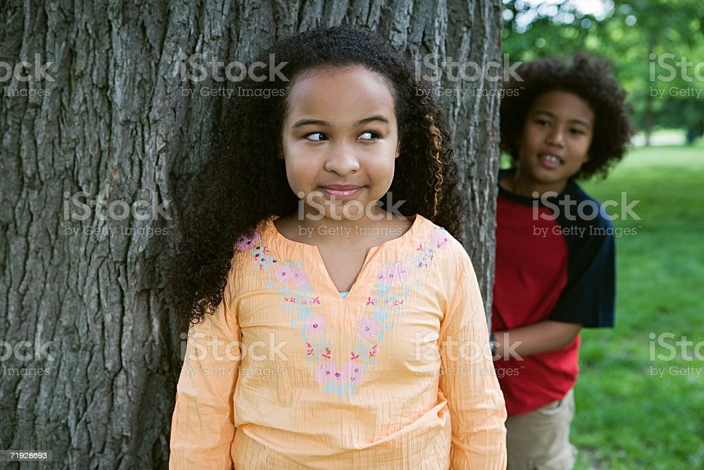 Girl and boy playing hide and seek royalty-free stock photo