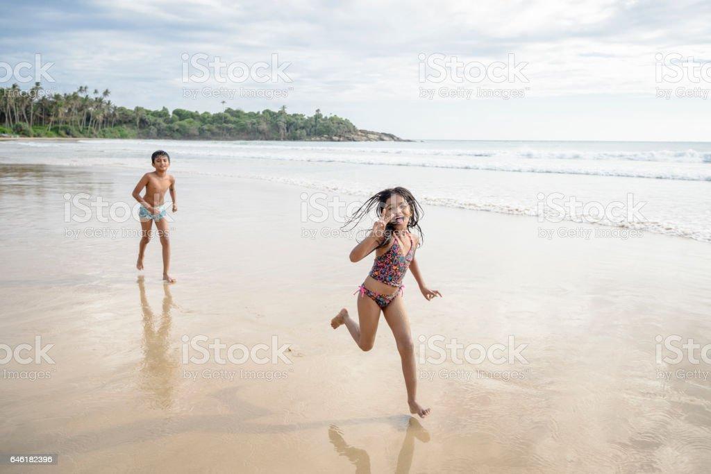Girl and boy playing on beach in swimwear stock photo