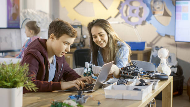 mädchen und jungen programm niedlichen kleine roboter mit laptop für ihren naturwissenschaftlichen unterricht in der schule. - versuche nicht zu lachen stock-fotos und bilder