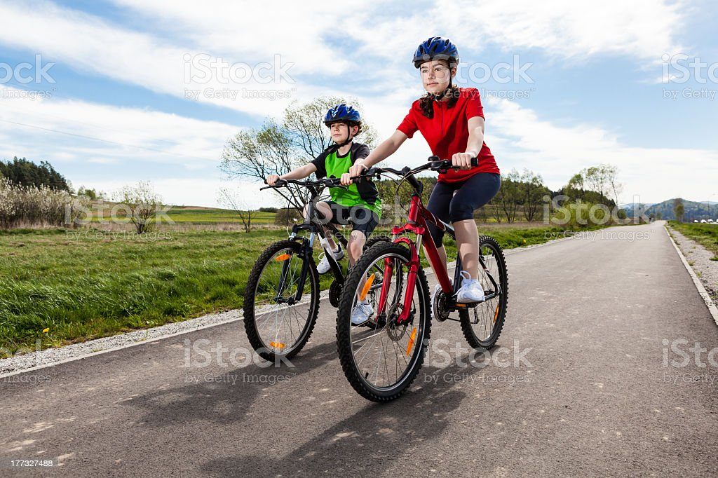 Girl and boy ride their bikes on a country road stock photo