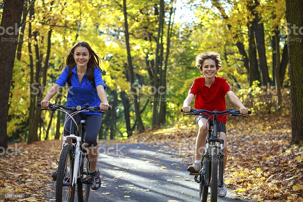 Girl and boy riding bikes in city park royalty-free stock photo
