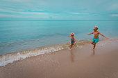 happy girl and boy running at beach, kids play at sea