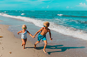 happy girl and boy running at beach, kids play with waves
