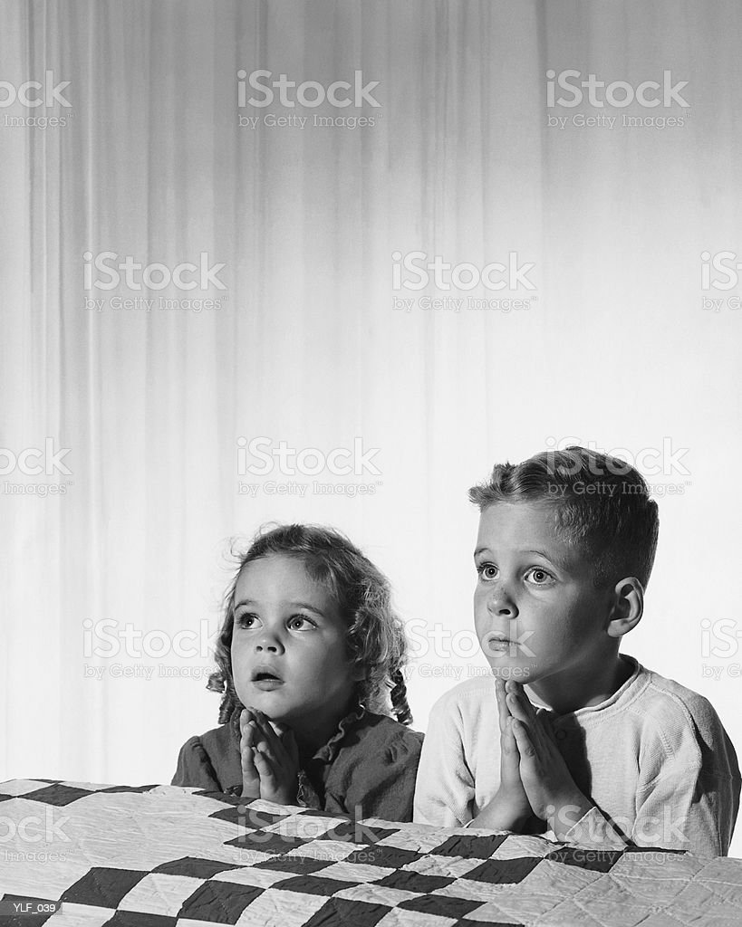 Girl and boy decir acostarse prayers foto de stock libre de derechos