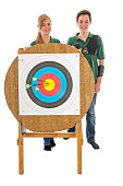 Young girl and boy standing behind the bull's eye of an archery target