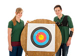 Young girl and boy standing besides the bull's eye of an archery target