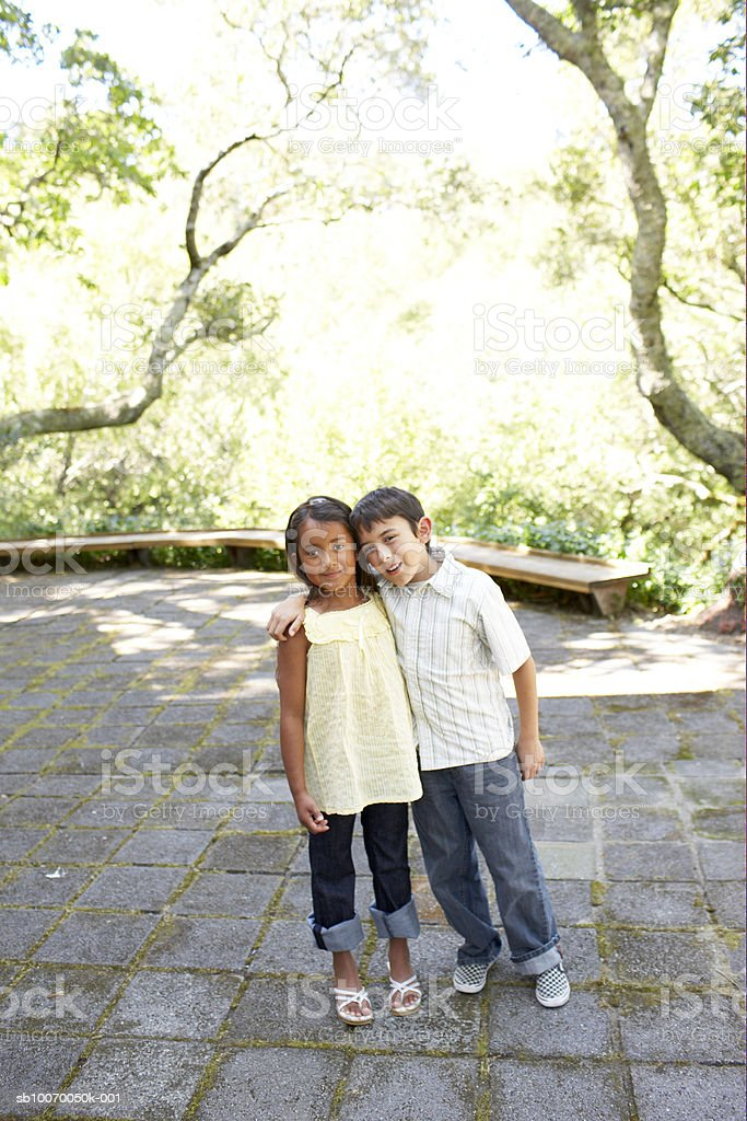 Girl and boy (6-11) standing with arm around, smiling, portrait royalty-free stock photo