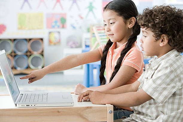 Girl and boy using laptop stock photo