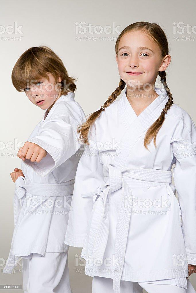 Ein Mädchen und ein Junge mit karate-Uniformen inspiriert Lizenzfreies stock-foto