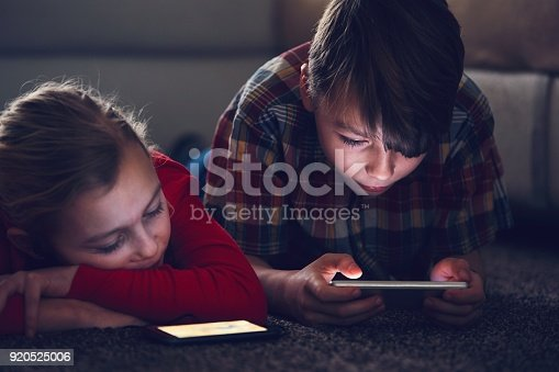 istock Girl and boy with their smart phones 920525006