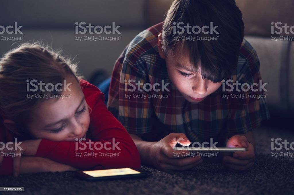 Girl and boy with their smart phones stock photo