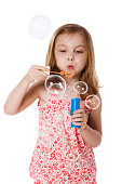 Happy Girl playing with soap bubbles isolated on white