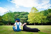 芝生の上に座っている少女とドーベルマン