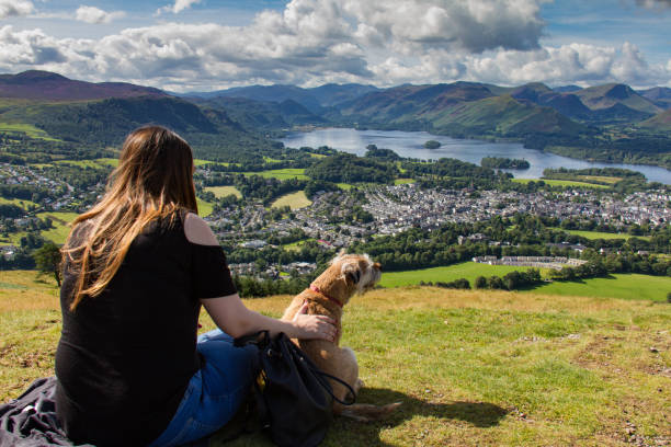 Girl and dog gazing at Keswick and Derwent Water, Cumbria stock photo
