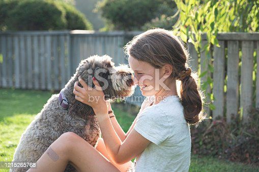 girl and dog showing affection to each other sitting in the garden and having a hug in the late afternoon