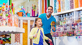 A little 6 year old boy smiling with his mother, standing in a candy store, surrounded by jars, containers and displays of colorful candies. The child is mixed race Hispanic and Caucasian.