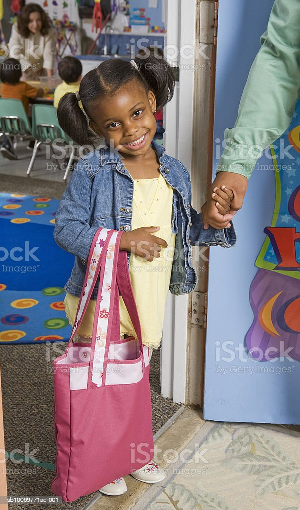 Girl (4-5) and father in doorway of classroom royalty-free stock photo