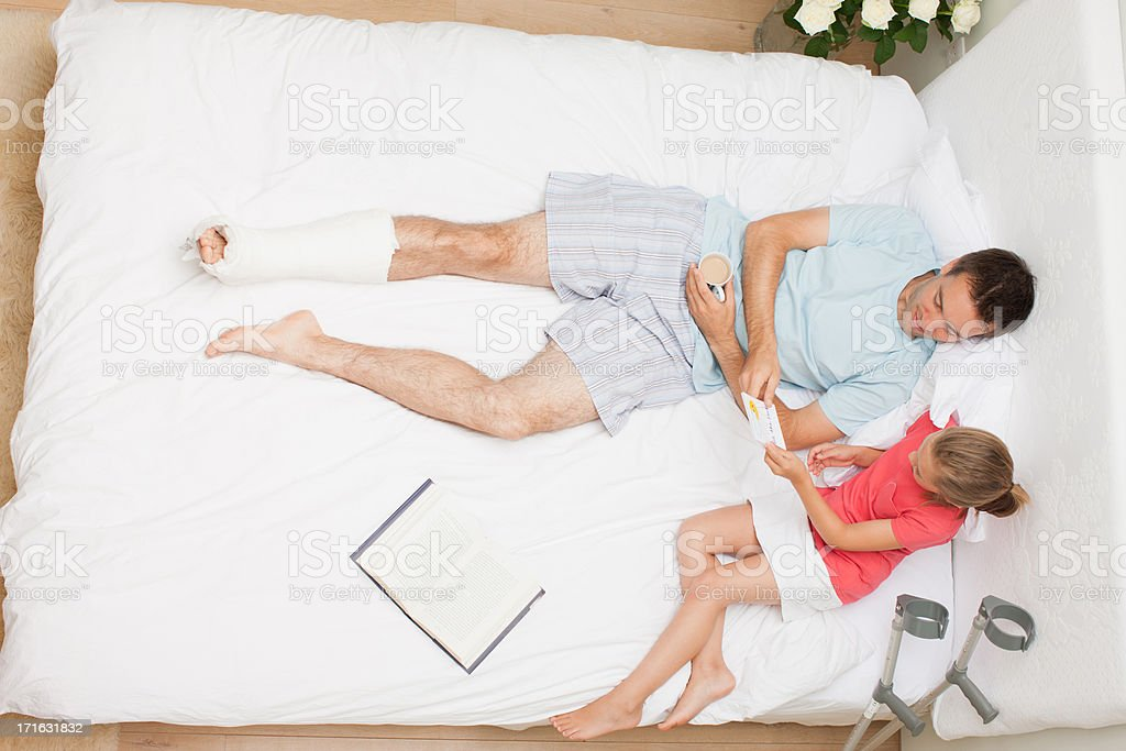 Girl and  father laying in bed with looking card stock photo