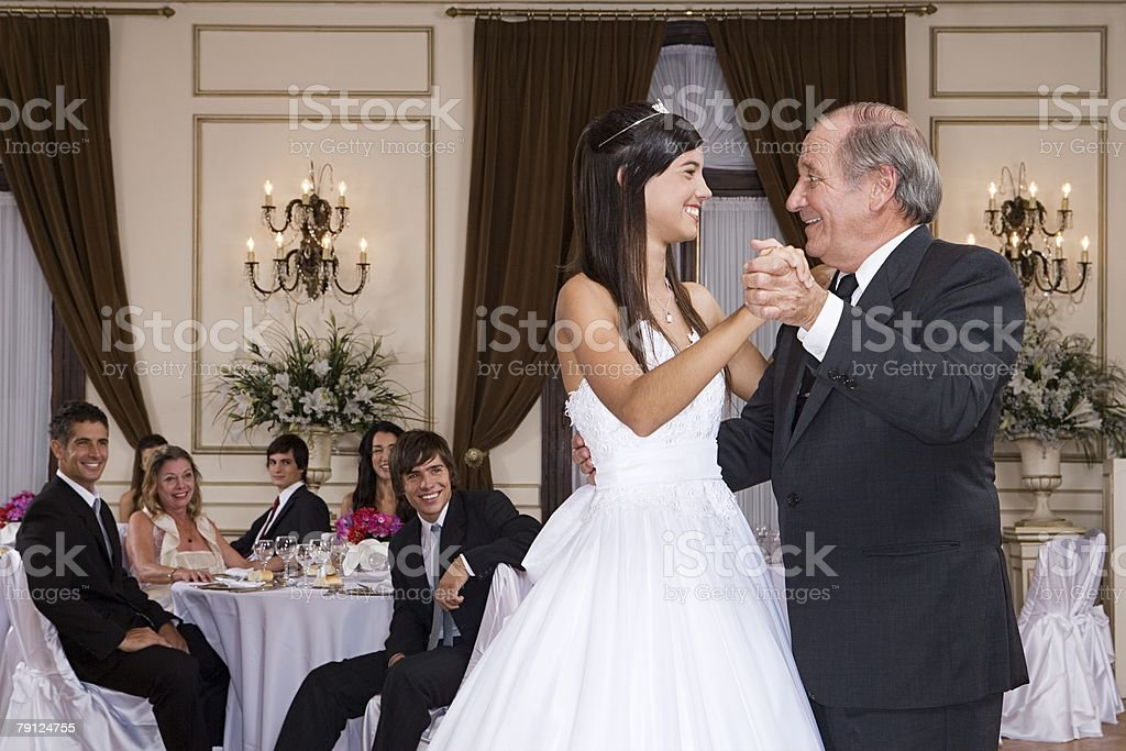 Girl and grandfather dancing at quinceanera stock photo