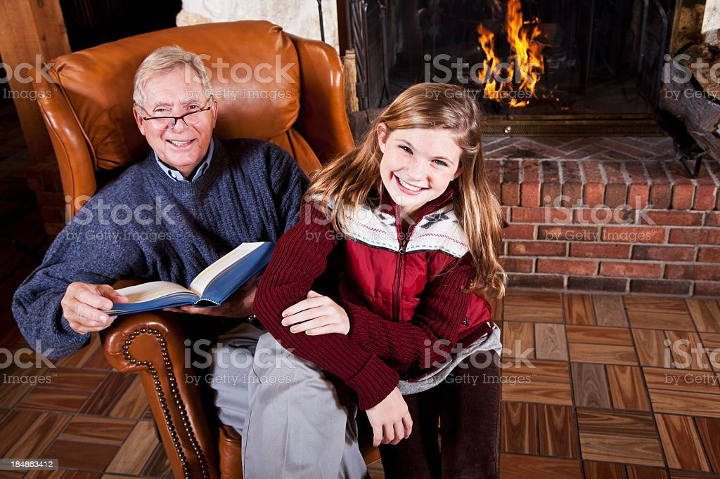 Girl and grandfather reading by fireplace stock photo