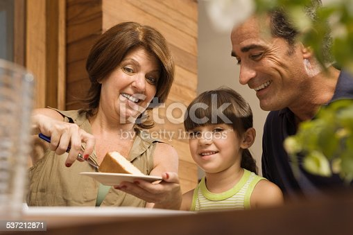 Girl and grandparents having cake