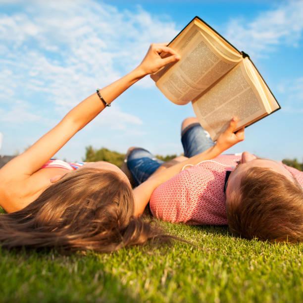 meisje en jongen liggend op het gras, lezen van een boek ontspannen in het park - newspaper beach stockfoto's en -beelden