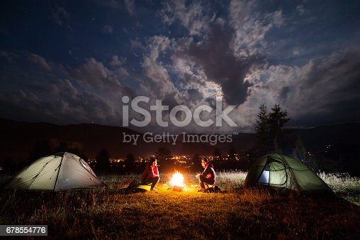 Girl and guy sitting at a bonfire near tents in the evening under incredibly beautiful a cloudy sky in the background mountains and luminous town