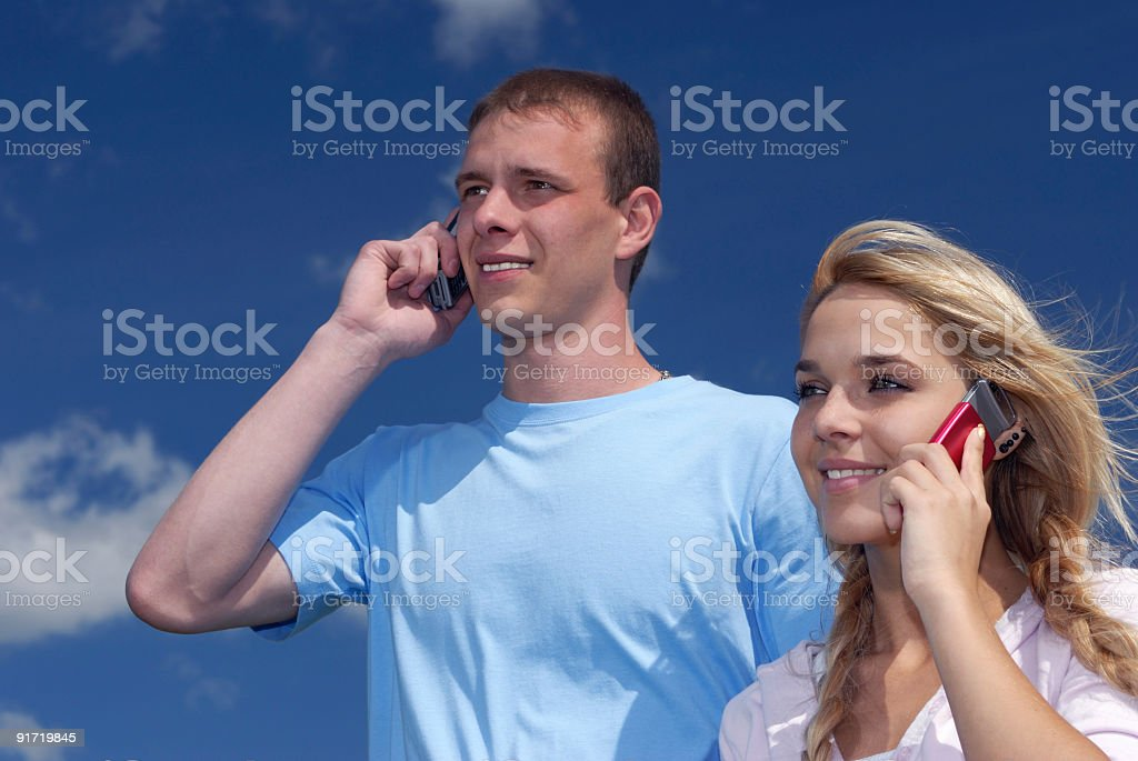 Girl and guy speak by a mobile phone royalty-free stock photo