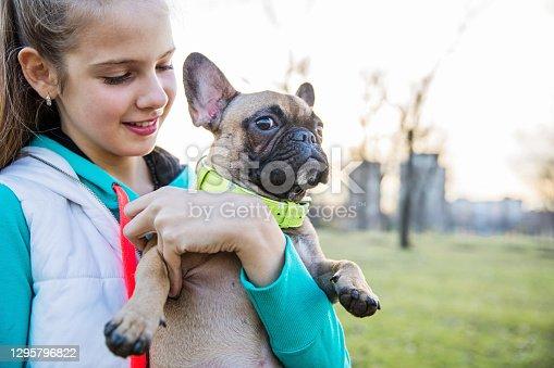 preteen girl holding her French Bulldog puppy