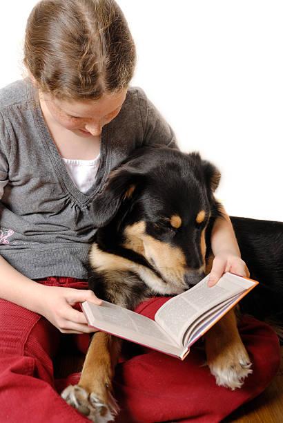 Mädchen und Ihr Hund liest ein Buch – Foto