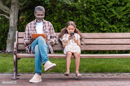 istock girl and her grandfather using smartphone and digital tablet 834343272