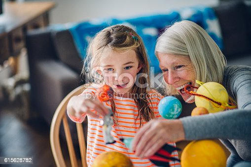Little girl and her grandma playing with a homemade planetarium. She holds an astronaut while her grandmother holds the spacecraft. Laughing and sitting close together as they enjoy playing lets pretend.