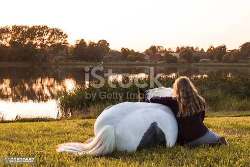 A girl and her horse sitting by the lake enjoying the golden sunset.